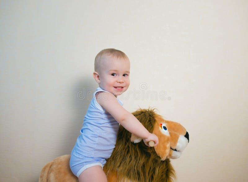 在狮子玩具的逗人喜爱的小男婴骑马 愉快的儿童情感 免版税库存照片
