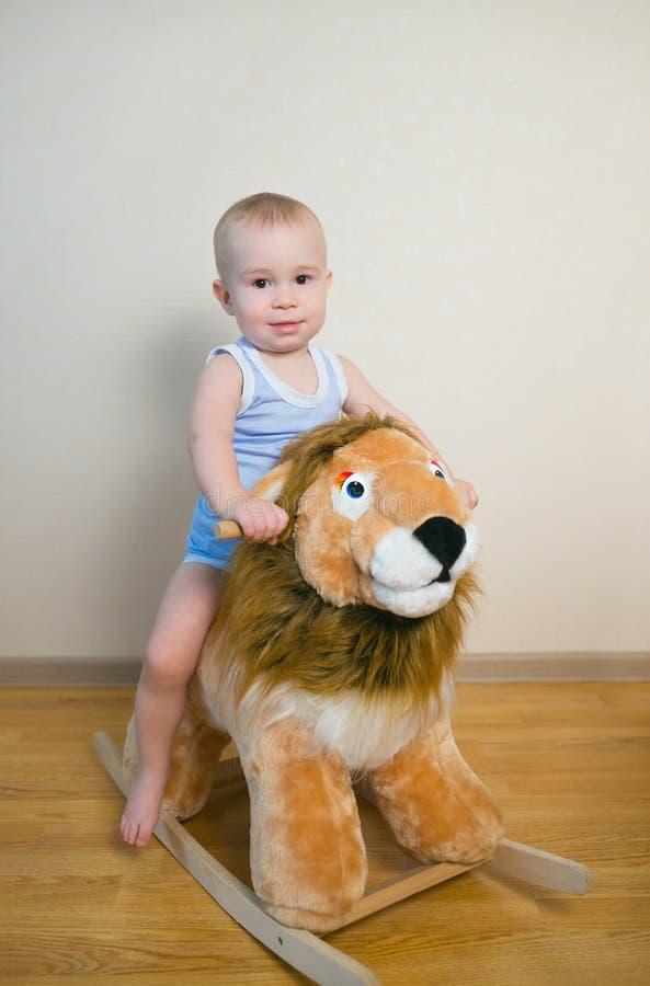 在狮子玩具的逗人喜爱的小男婴骑马 愉快的儿童情感 图库摄影