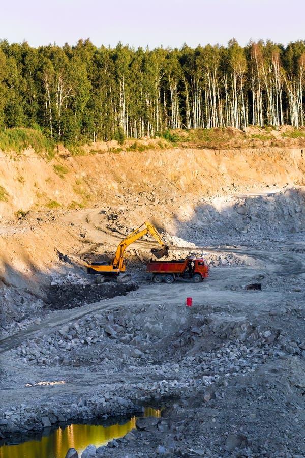在猎物的挖掘机在卡车装载岩石地面 库存图片