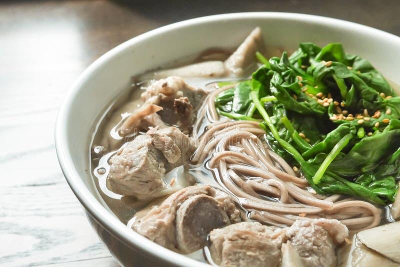 在猪排汤的Soba面条用菠菜 图库摄影