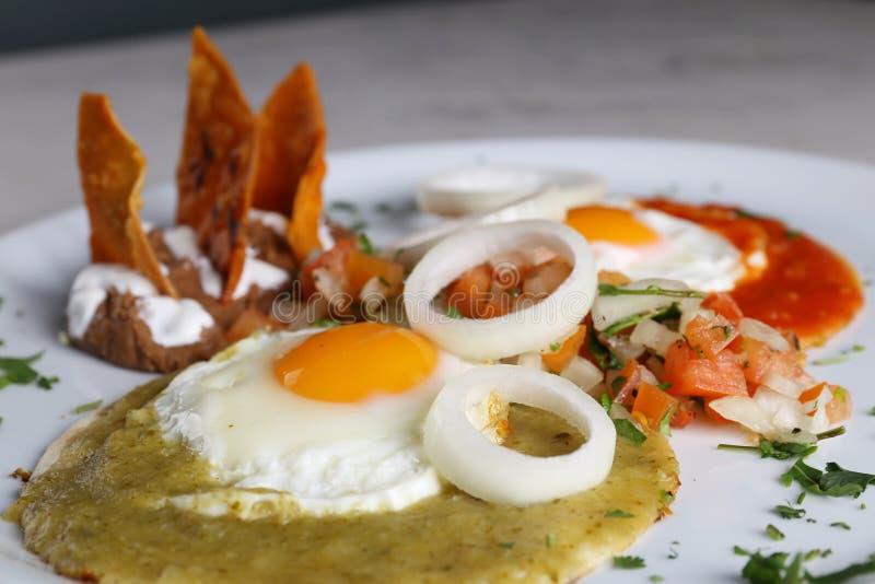在玉米粉薄烙饼的荷包蛋与辣调味汁verde和roja,墨西哥早餐 库存图片