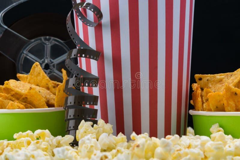 在玉米花背景是有芯片的纸杯电影的 免版税库存图片