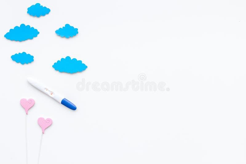 在玩具云彩附近的正面妊娠试验和心脏在白色背景顶视图拷贝空间签字 库存图片