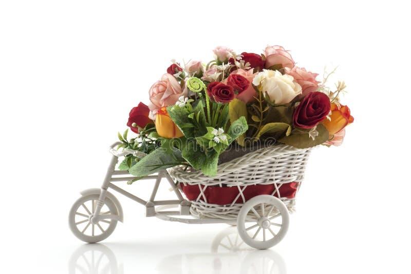 在玩具在白色背景隔绝的自行车花瓶的人造花 库存照片