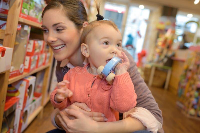 在玩具店的年轻母亲女儿购物 库存图片