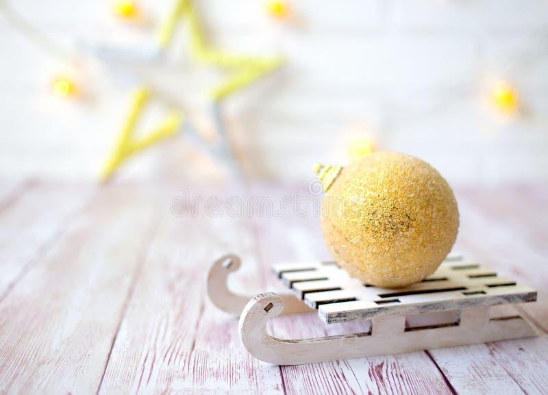 在玩具木雪撬的光亮的圣诞节球在轻的bokeh背景与goolden星 invitation new year 剪报装饰鹿查出的路径红色xmas 免版税库存图片