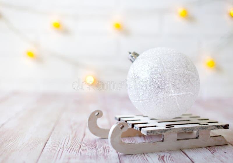 在玩具木雪撬的光亮的圣诞节球在轻的bokeh背景与goolden星 invitation new year 剪报装饰鹿查出的路径红色xmas 库存图片