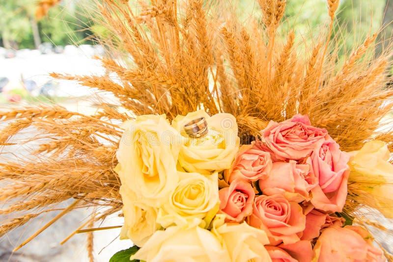 在玫瑰花束和麦子耳朵的婚戒 库存照片