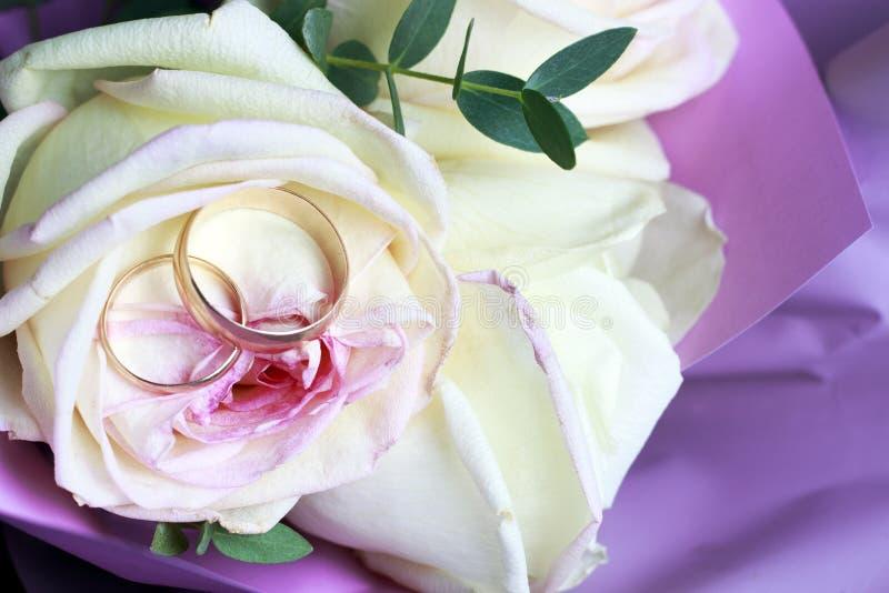 在玫瑰花束,婚姻的概念的金黄结婚戒指 库存图片