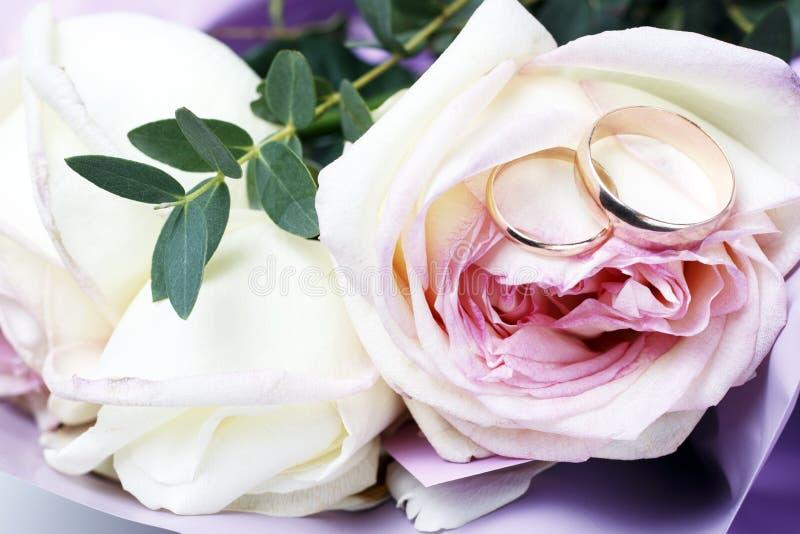 在玫瑰花束,婚姻的概念的金黄结婚戒指 免版税库存照片