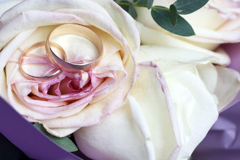 在玫瑰花束,婚姻的概念的金黄结婚戒指 免版税库存图片