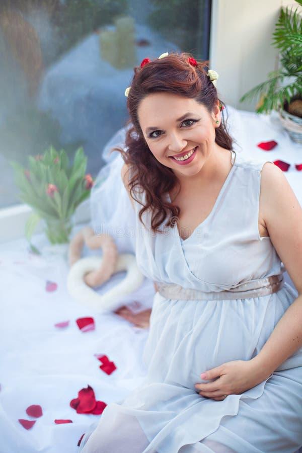 在玫瑰花瓣中的相当微笑的孕妇 免版税库存照片