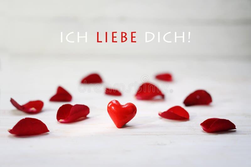 在玫瑰花瓣在浅灰色的木背景,德国文本Ich Liebe Dich之间的红色玻璃心脏,意味我爱你 免版税库存图片