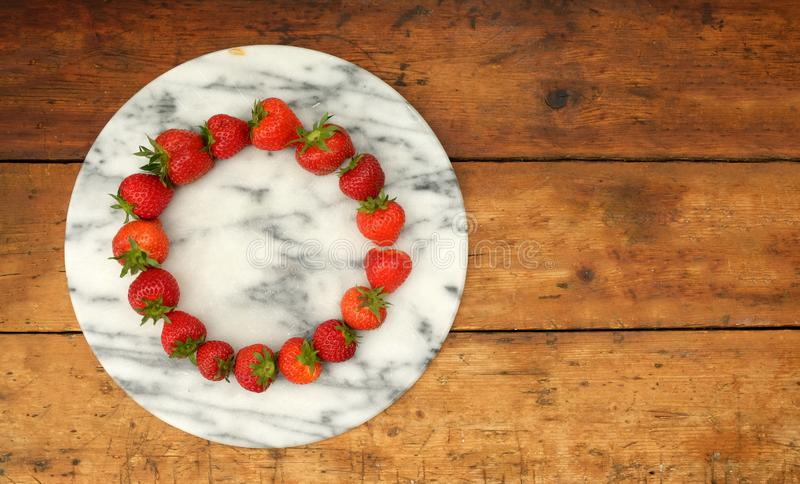 在环形轧材安置的十六个草莓在一个大理石圆委员会 免版税库存图片