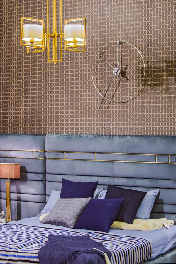在现代之字形的样式的卧室内部,有减速火箭的墙纸的葡萄酒卧室,现代豪华枝形吊灯和床 免版税图库摄影
