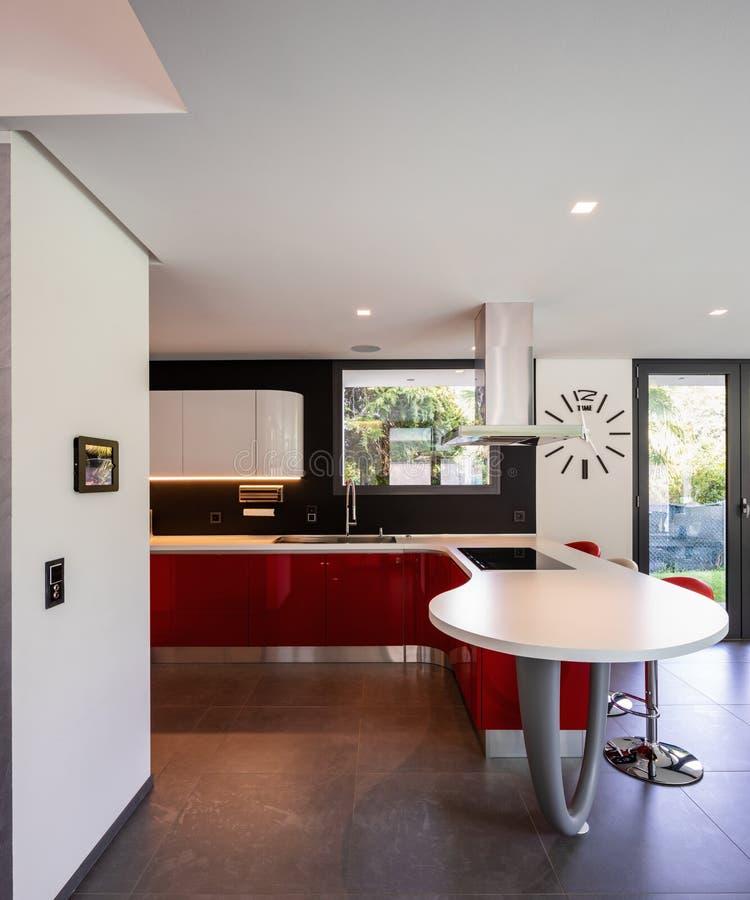 在现代别墅的红色厨房细节 图库摄影