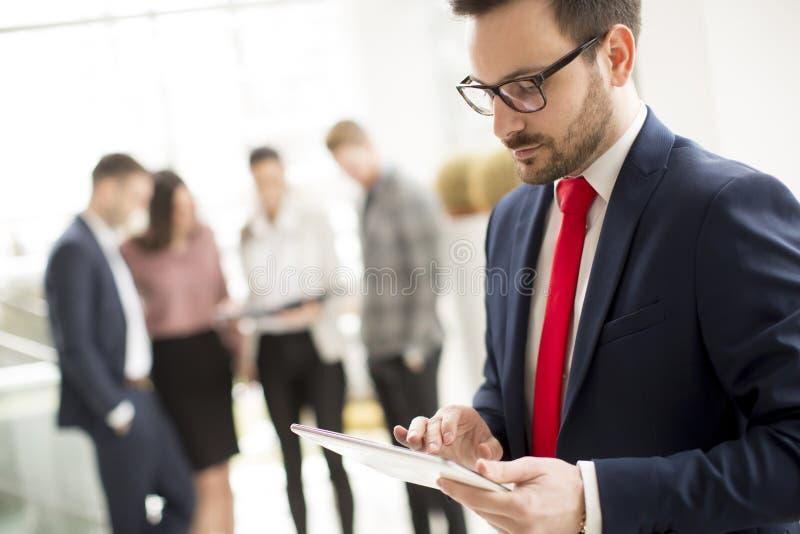 在现代办公室和使用片剂的衣服身分穿戴的勤勉商人 免版税库存图片