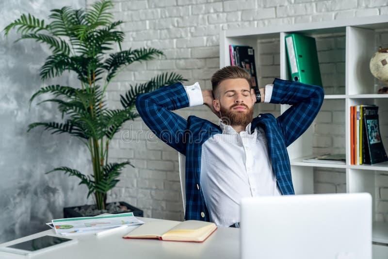 在现代办公室里休息的留胡子的时髦男人 库存照片