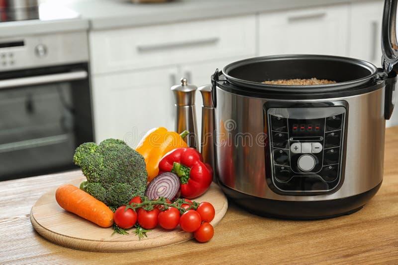 在现代多烹饪器材的可口在木桌上的荞麦和产品 图库摄影