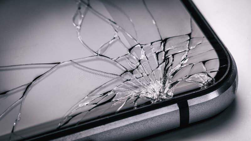 残破的流动手机屏幕 在现代小配件的微弱的玻璃 免版税库存照片