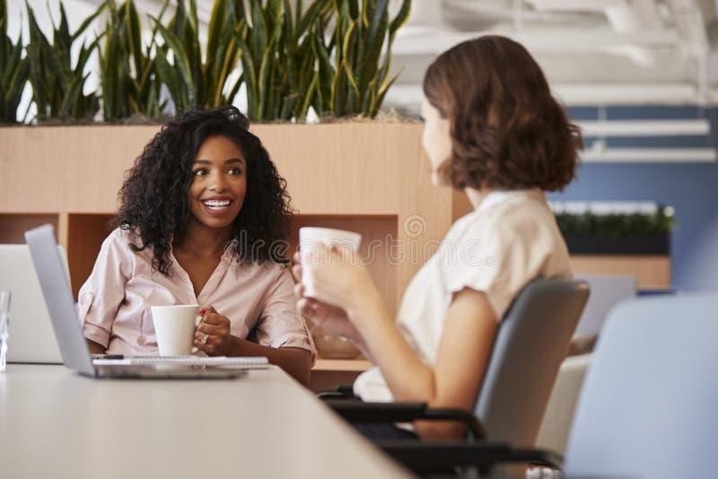 在现代开放学制办事处饮用的咖啡的表上的两名女实业家 库存图片