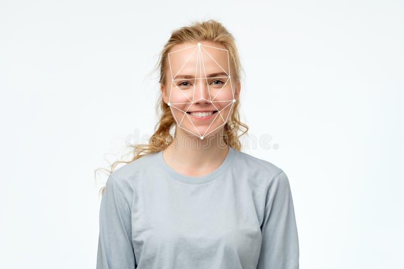 在现代技术概念的面貌识别 愉快的白肤金发的女孩画象  库存照片