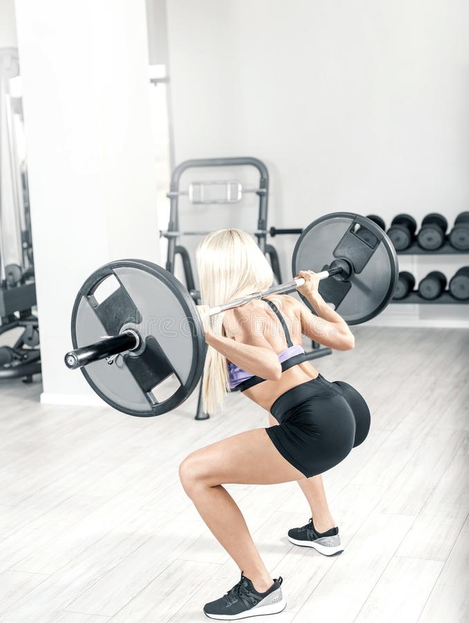 在现代明亮的健身房的白肤金发的做的蹲坐 库存图片