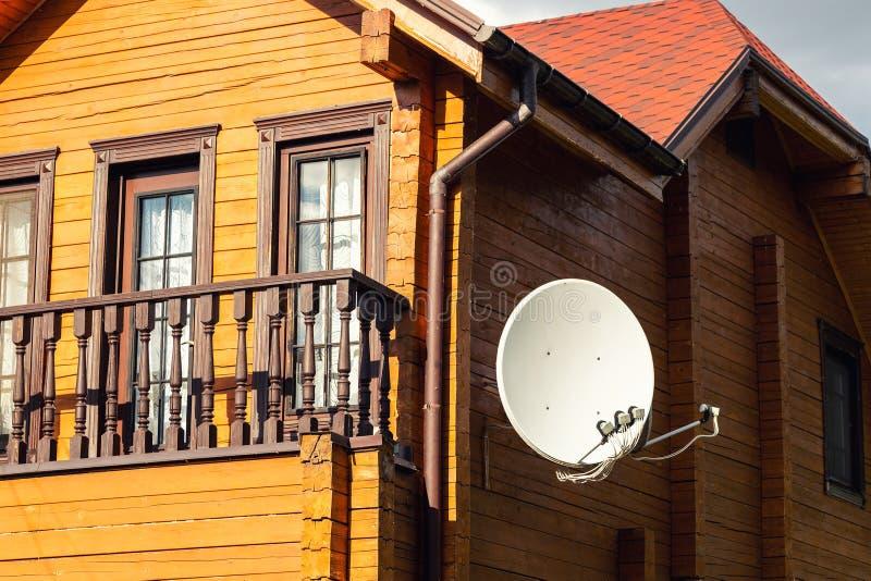 在现代木乡间别墅别墅墙壁上垂悬的白色抛物面卫星antena盘  无线电视播送 免版税库存图片