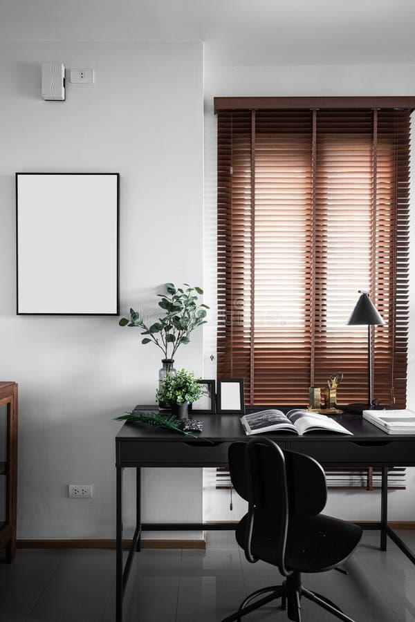 在现代样式的运作的角落与黑喷漆工作表空的框架安装在白色被绘的墙壁/工作场所/interi 图库摄影