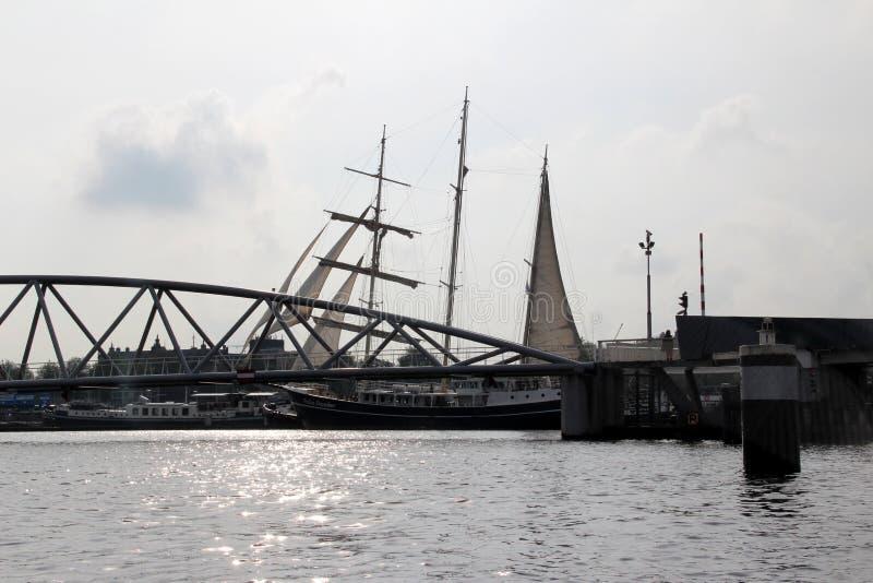 在现代桥梁建筑的看法有风帆的在背景中在河在阿姆斯特丹荷兰 图库摄影