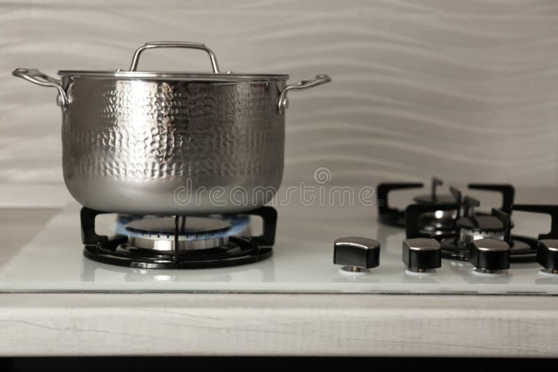 在现代煤气炉的发光的钢平底深锅 库存图片