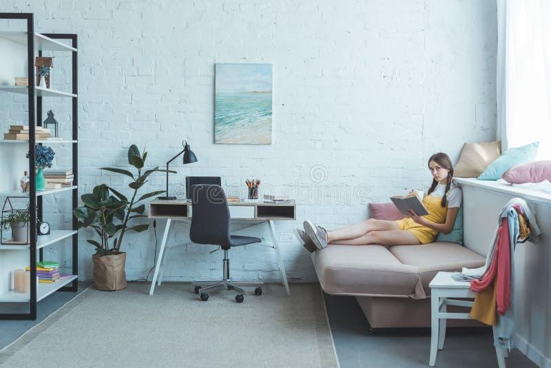 在现代的青少年的女孩看书 免版税图库摄影