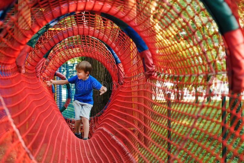 在现代绳索冒险公园的愉快的孩子 E o 免版税库存照片