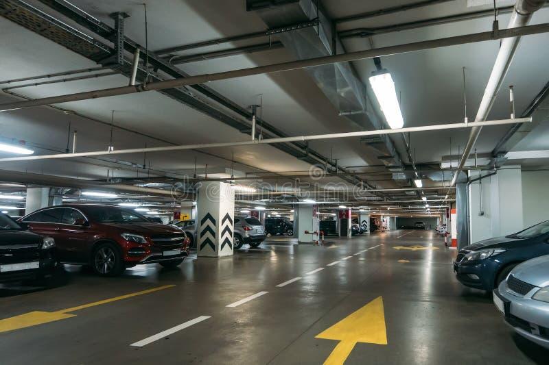 在现代购物中心下的被阐明的地下汽车停放的内部与许多车和箭头在地板上 图库摄影