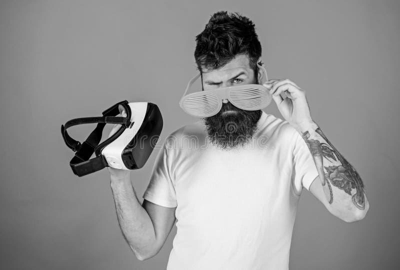 在现实和VR之间的选择 供以人员有虚拟现实耳机和装有百叶窗板的太阳镜的有胡子的行家在红色 免版税图库摄影