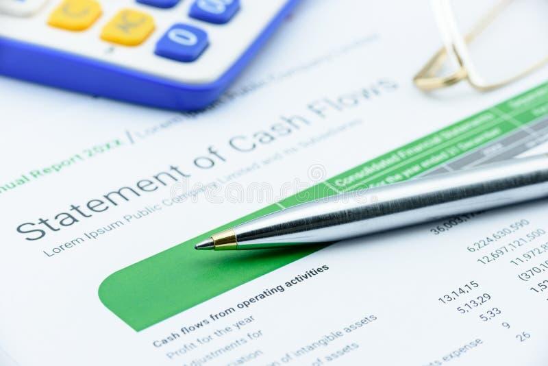 在现金流量说明的蓝色圆珠笔与眼睛玻璃和计算器的 免版税库存照片