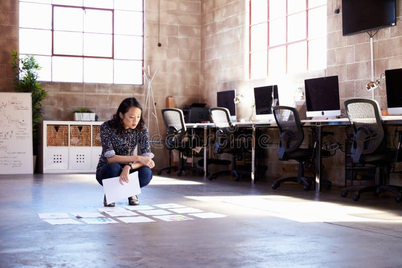 在现代办公室地板上的女性设计师计划布局  图库摄影
