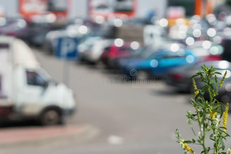 在现代商城旁边的被弄脏的室外停车处,晴朗的夏日,季节销售的抽象背景 免版税库存照片
