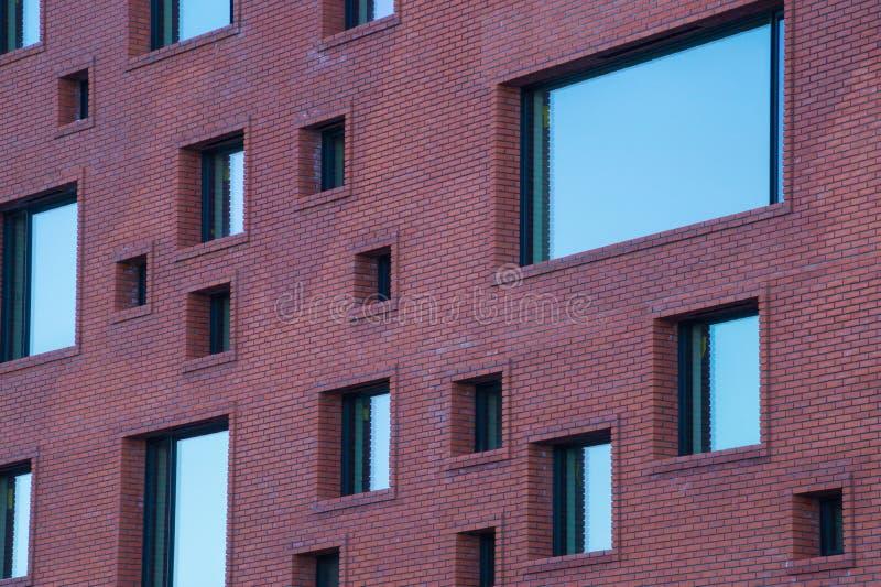 在现代大厦砖墙上的奇怪的大小的窗口  免版税库存图片