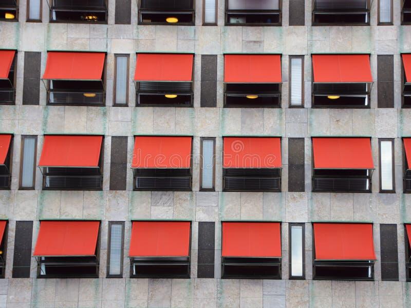 在现代大厦门面的十二个红色遮光罩 免版税图库摄影