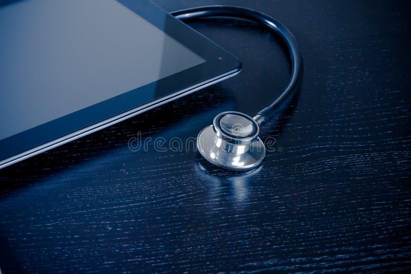 在现代数字式片剂个人计算机的医疗听诊器在木桌上的实验室 免版税库存图片
