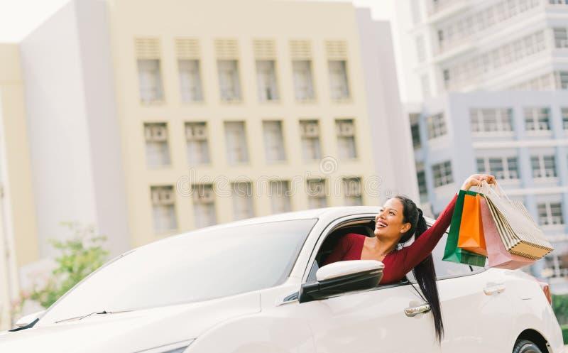 在现代白色汽车的愉快的亚洲旅游妇女培养购物袋,注视着拷贝空间 Shopaholic消费者至上主义活动 库存照片