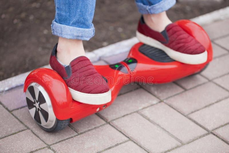 在现代红色电微型segway或翱翔委员会滑行车的女孩骑马 图库摄影