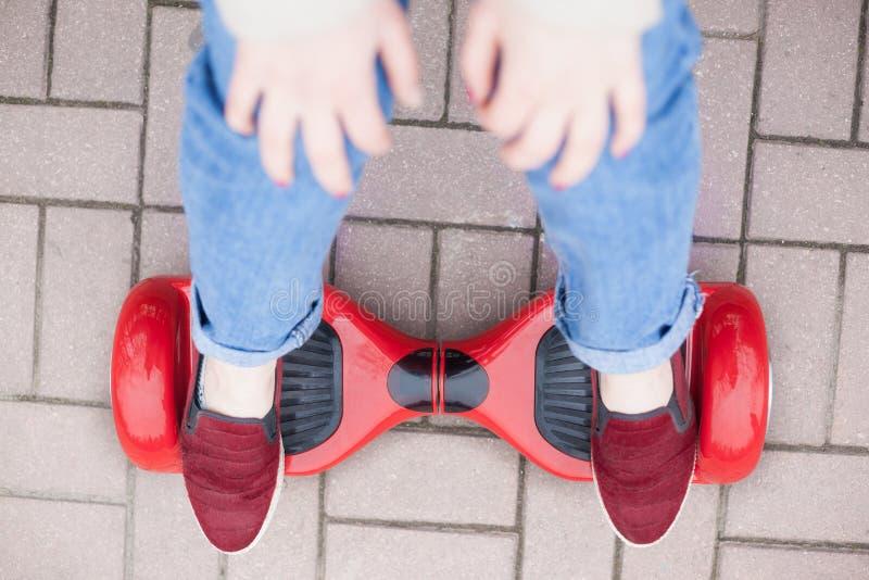 在现代红色电微型segway或翱翔委员会滑行车的女孩骑马 库存图片