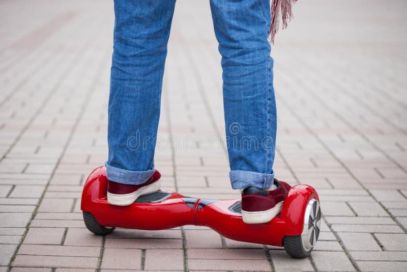在现代红色电微型segway或翱翔委员会滑行车的妇女骑马 免版税图库摄影