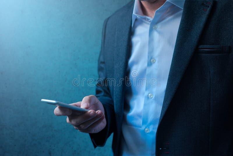 在现代西装的英俊的商人使用手机 免版税库存图片