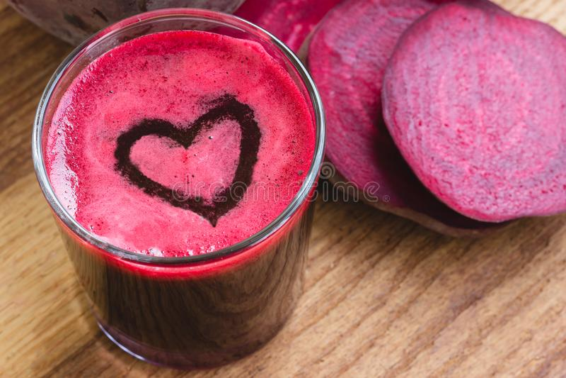 在玻璃、心脏形状泡沫和切的甜菜根的新鲜的甜菜汁在木桌上 库存图片