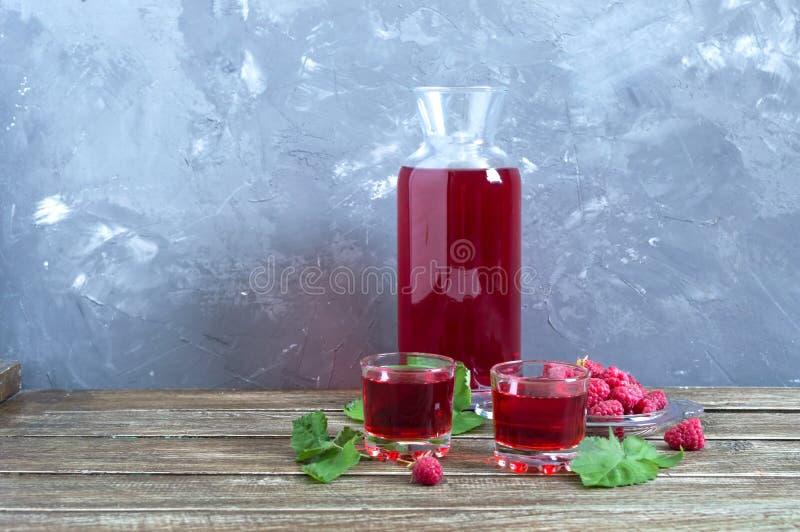 在玻璃、新鲜的自然成熟有机莓果和绿色叶子的莓利口酒在土气木背景 酒客调味 图库摄影