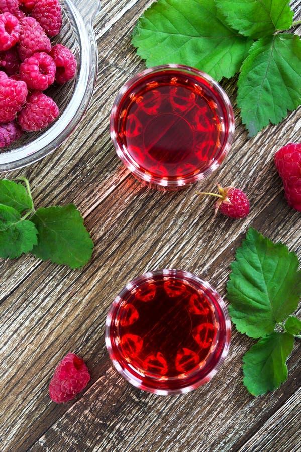 在玻璃、新鲜的自然成熟有机莓果和绿色叶子的莓利口酒在土气木背景 酒客调味 库存照片