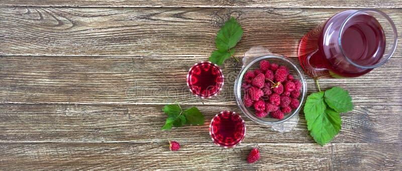 在玻璃、新鲜的自然成熟有机莓果和绿色叶子的莓利口酒在土气木背景 酒客调味 免版税库存照片